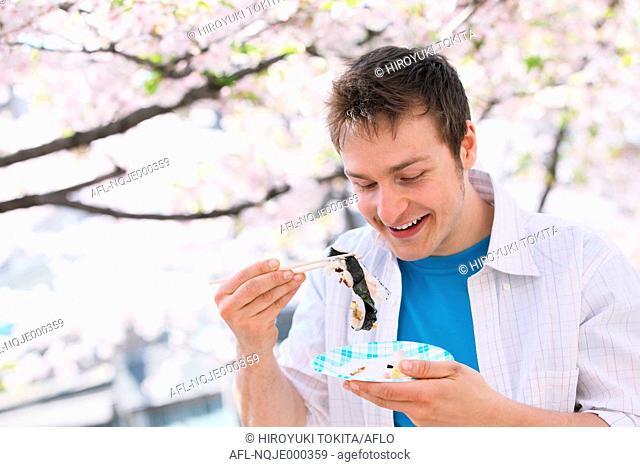 Caucasian man eating sushi with chopsticks during hanami season
