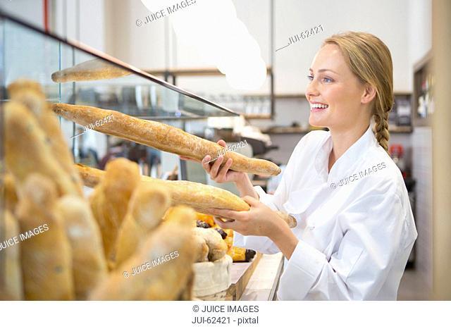 Smiling baker holding bread in bakery