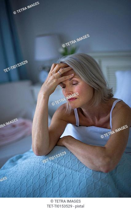 Senior woman sitting in bed and suffering from headache
