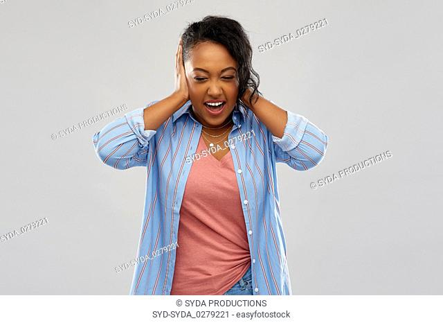 african american woman closing ears by hands