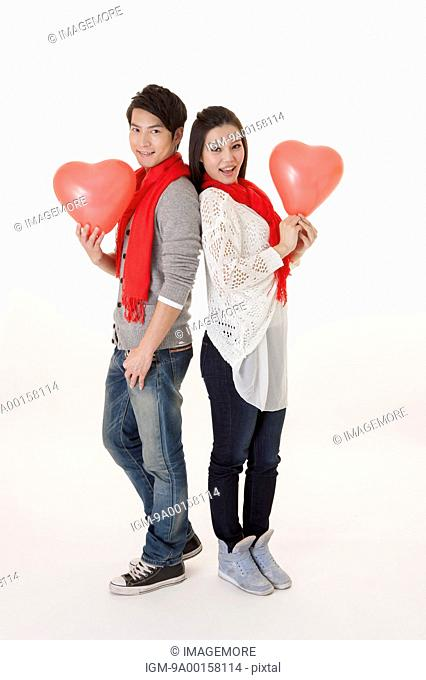 Young couple holding heart-shaped balloon and smiling at the camera