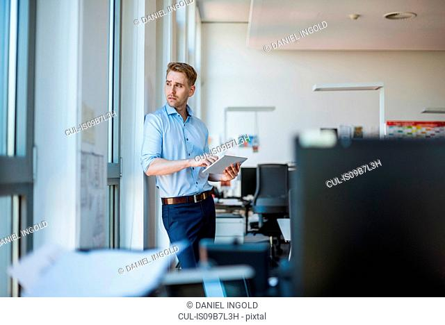 Mid adult businessman using digital tablet while looking back through window