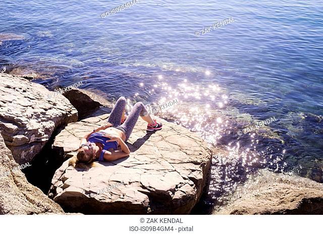 Woman sunbathing on rocks by sea