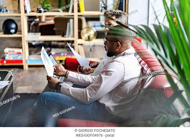 Two businessmen using laptop and discussing documents on sofa in loft office