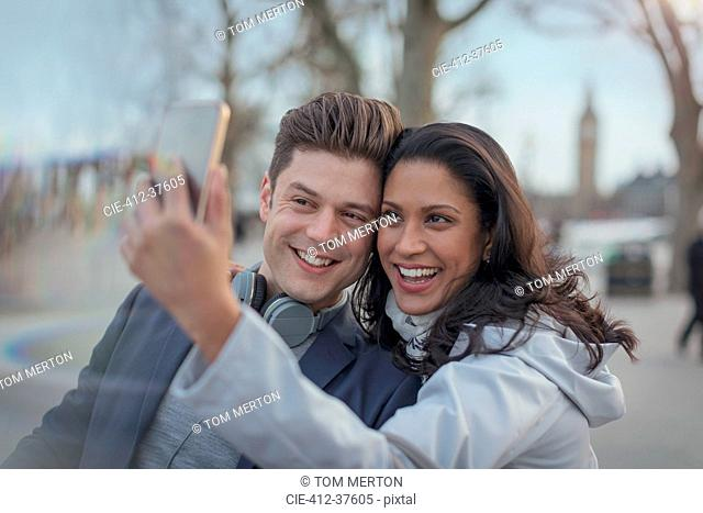 Smiling couple taking selfie with camera phone in urban park