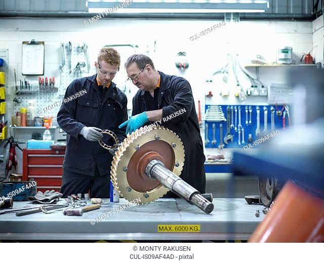 Engineer teaching apprentice in engineering factory