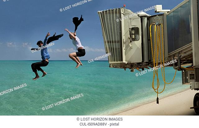 Couple jumping out of airport bridge onto seashore