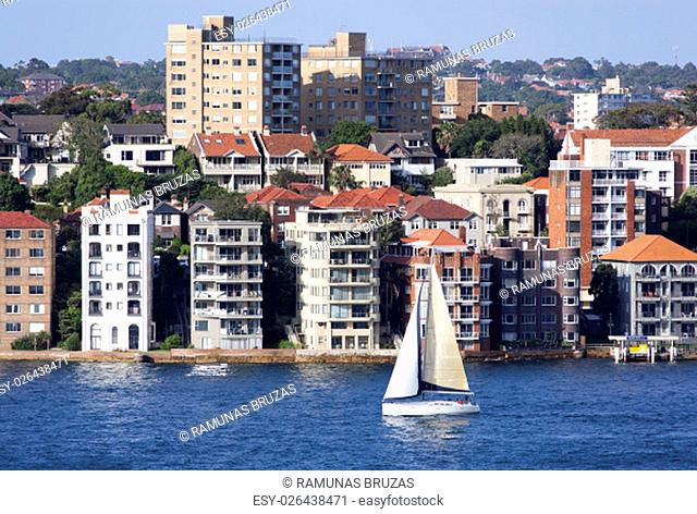 The yacht passing by North Sydney residential district (New South Wales, Australia)