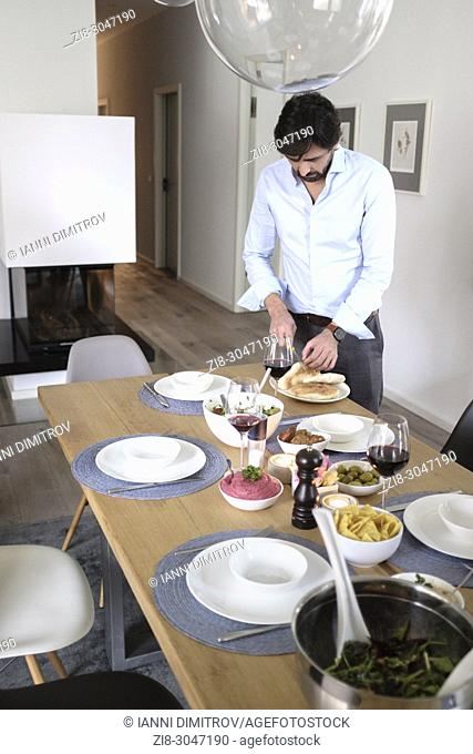Man setting dinnertable with vegetarian food