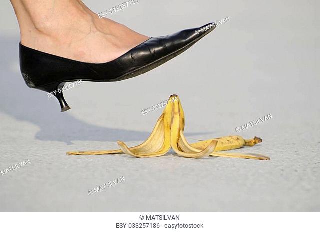 woman with high heels shoes walking on banana peel