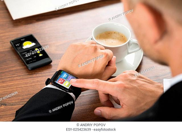 Close-up Of A Businessman Checking Weather On Smartwatch