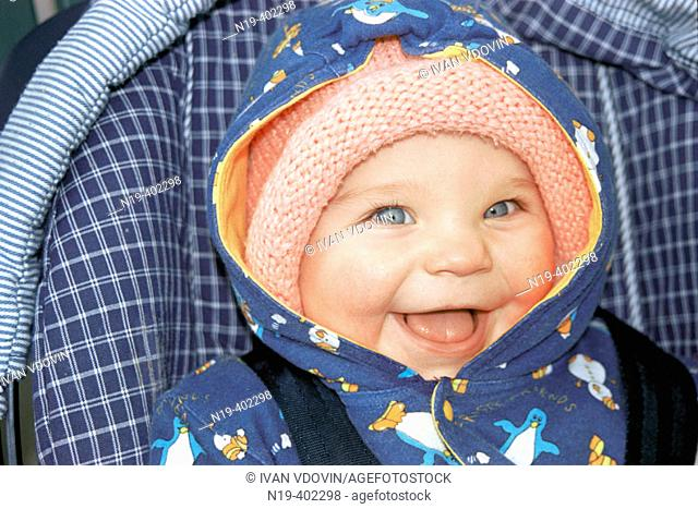 Girl in a knitted cap laughs