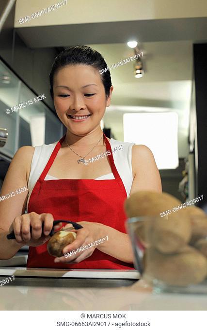 Chinese woman peeling a potato in kitchen