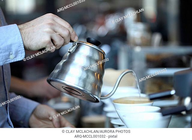 Barista holding kettle while preparing pour over coffee in coffee shop by pouring water from kettle into coffee filter, Castelvetro Di Modena, Emilia-Romagna