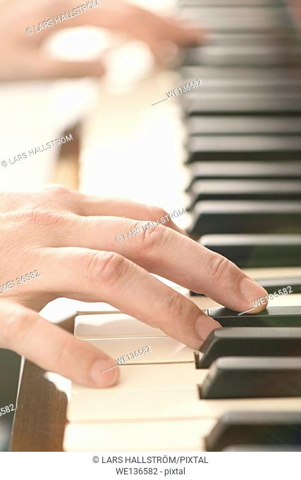 Close up of hands of man playing the piano