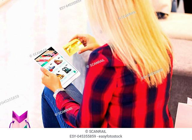 Young blonde woman with long hair shopping online with tablet computer and credit card in the fashion store and making purchase and payment