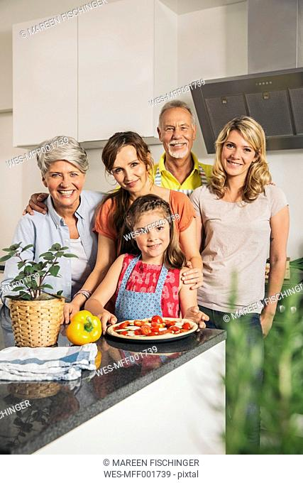 Group picture of three generations family in the kitchen