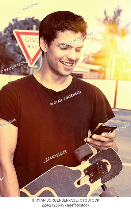 Retro photo with yellow sun flare of a happy Latin American man holding skate board while connecting online to social media with mobile smartphone