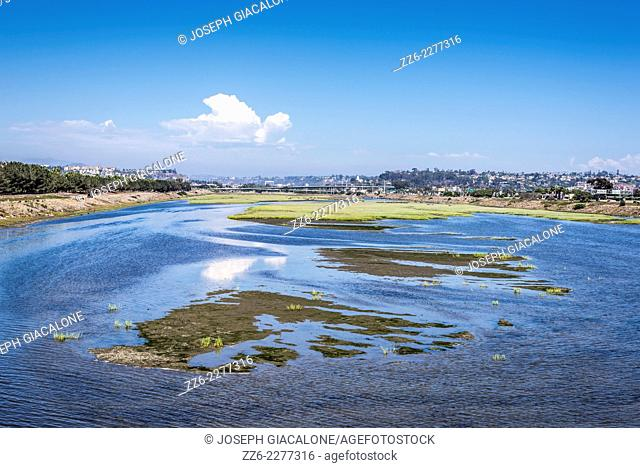 View looking down on the San Diego River with a thundercloud in the background. San Diego, California, United States