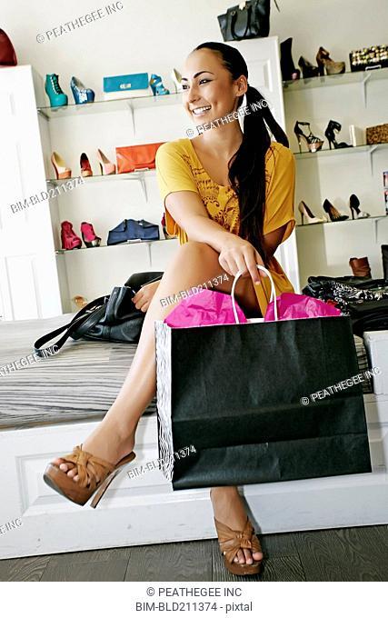 Mixed race woman shopping in shoe store