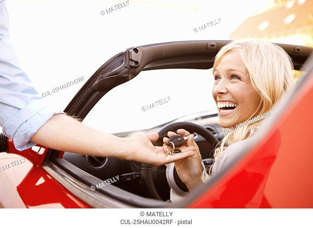 Girl receiving keys to an electric car