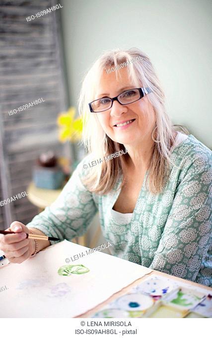 Portrait of mature female artist watercolour painting in studio