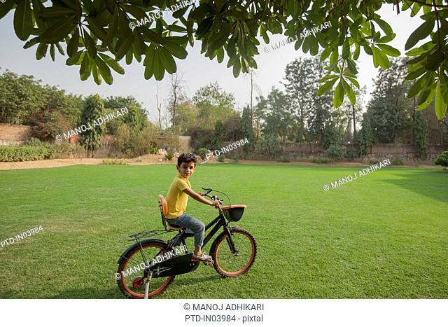 India, Young boy (4-5) cycling on backyard
