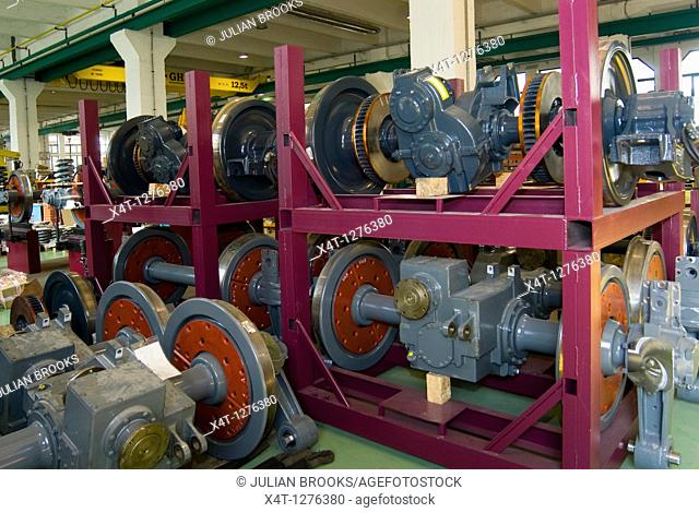 Railway wheels being stored in preparation for assembly  These are the driving wheels with gearboxes attached