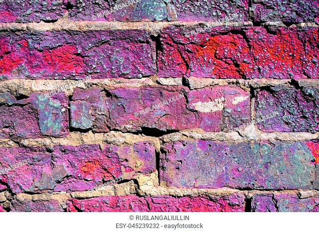 Old broken brick wall close-up, toned image in purple