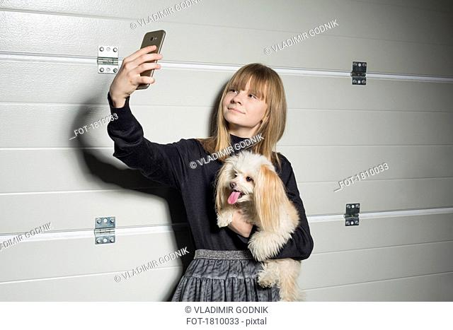 Girl with dog taking selfie with camera phone in garage