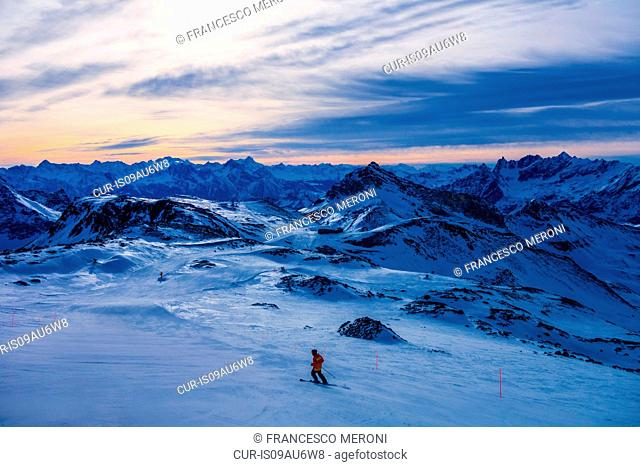 Skier in mountains at dusk, Cervinia, Italy