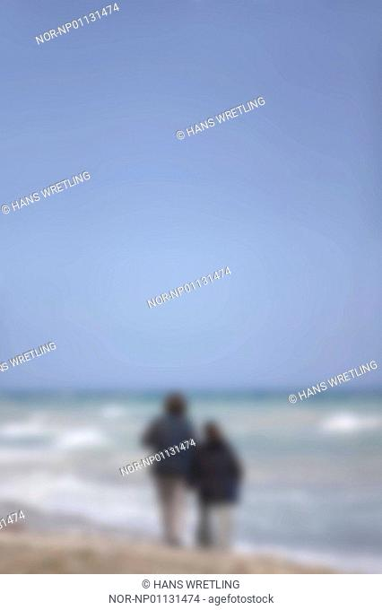 Rear view of two people standing on the beach