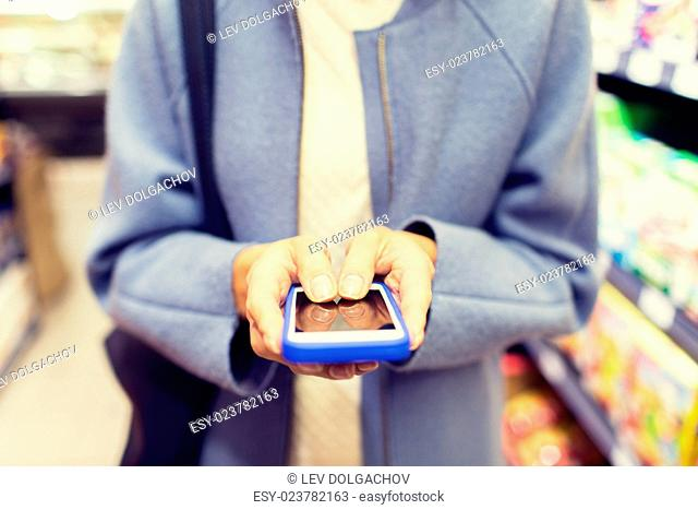 sale, shopping, consumerism and people concept - close up of woman with smartphone choosing and buying food in market