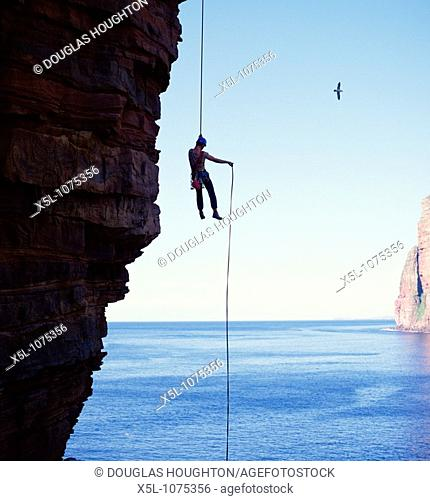 ABSEILING SPORT Abseiler descending Old Man of Hoy seastack Orkney