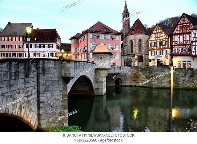 Henkerbrucke - Henker bridge over Kocher river, traditional historic half-timbered townhouses and church Johanniterkirche in background