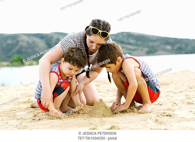 Mother playing with sons (4-5, 6-7) on beach by lake