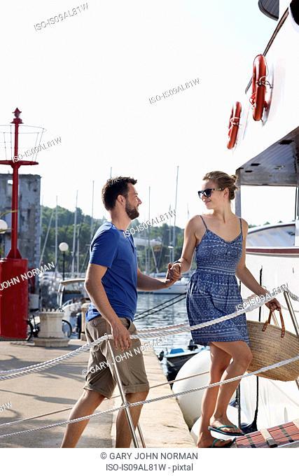 Young couple boarding boat, Milna, Brac, Croatia