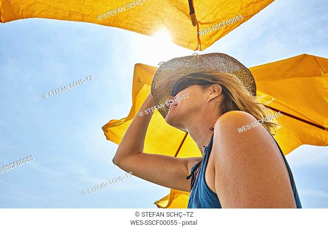 Smiling woman wearing straw hat under sunsahde in sunlight