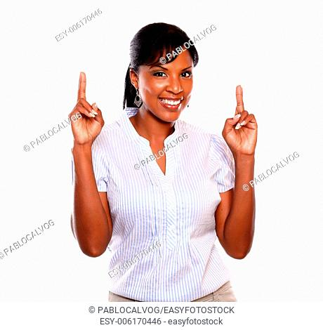 Pretty young woman crossing fingers while is looking at you on isolated background