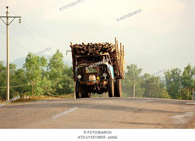 Truck carrying logs driving towards camera