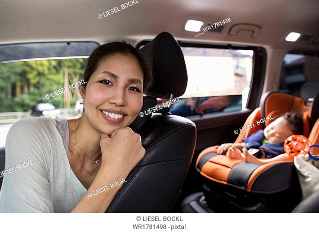 A mother and her young baby boy in a car