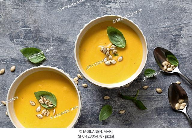 Pumpkin soup with roasted pumpkin seeds and basil
