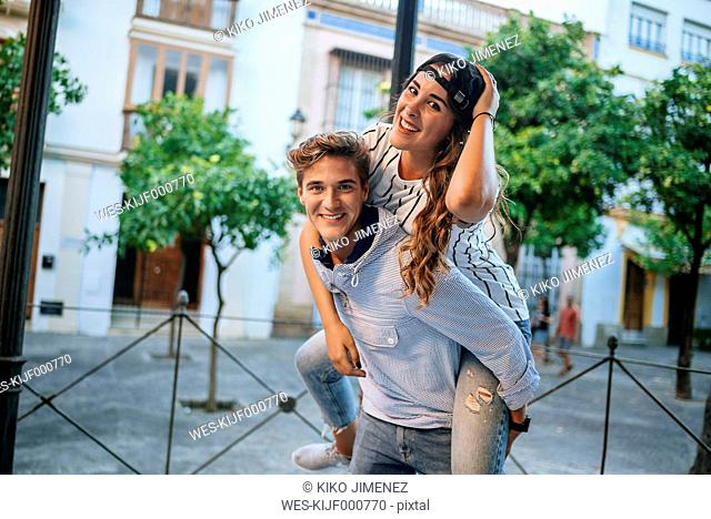 Happy young man giving his girlfriend a piggyback ride