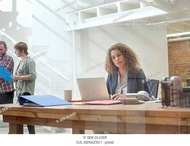 Young woman at desk typing on laptop in creative studio