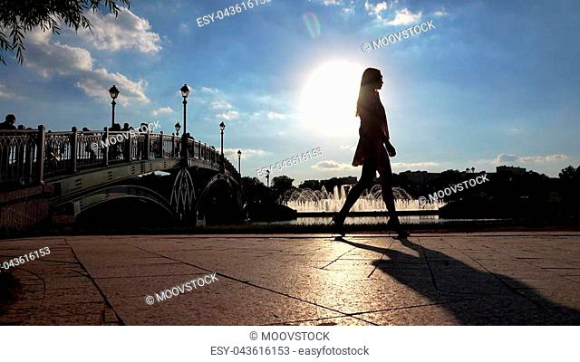 Silhouette of a slim girl in high heels walking on sunny park embankment