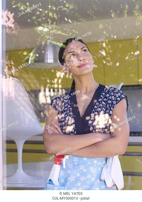 Young woman daydreaming whilst cleaning