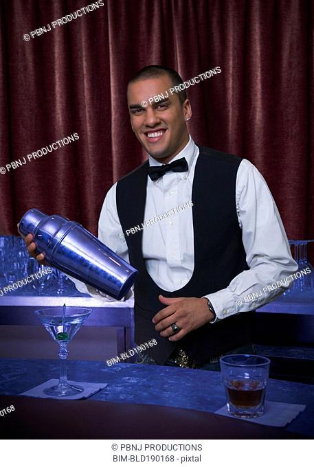 Hispanic bartender making cocktail