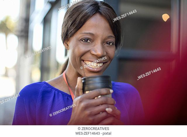 Portrait of smiling businesswoman with coffee mug