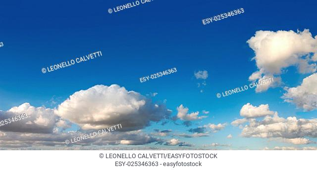 Blue sky with several cumulus white clouds in late afternoon. Cinemascope format