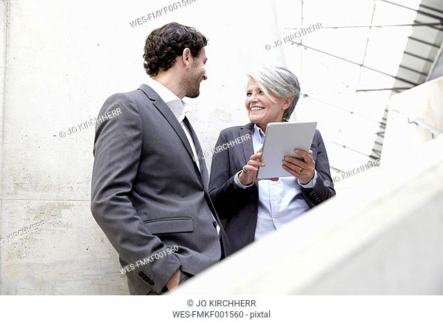Two business people with digital tablet in modern architecture